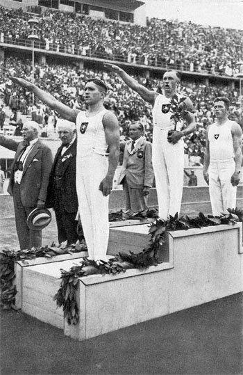 German athletes giving the Nazi salute on the medal stand in a stadium, likely after a track and field event, at the 1936 Summer Olympics.