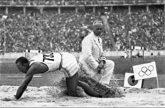 A long jumper competing in a stadium, at the 1936 Summer Olympics.