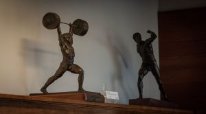 Two physical culture sculptures: a weightlifter pressing a barbell overhead with two hands, and a discus thrower, from the Weider Art Collection, in the Reading Room.