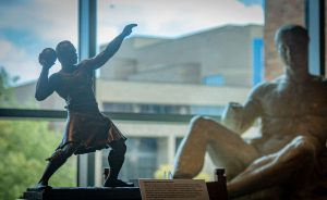 A sculpture of strongman Donald Dinnie about to throw the shot, in the Reading Room; a Battle Cast statue of a reclining man, on loan from the Blanton Museum of Art, is in the background.