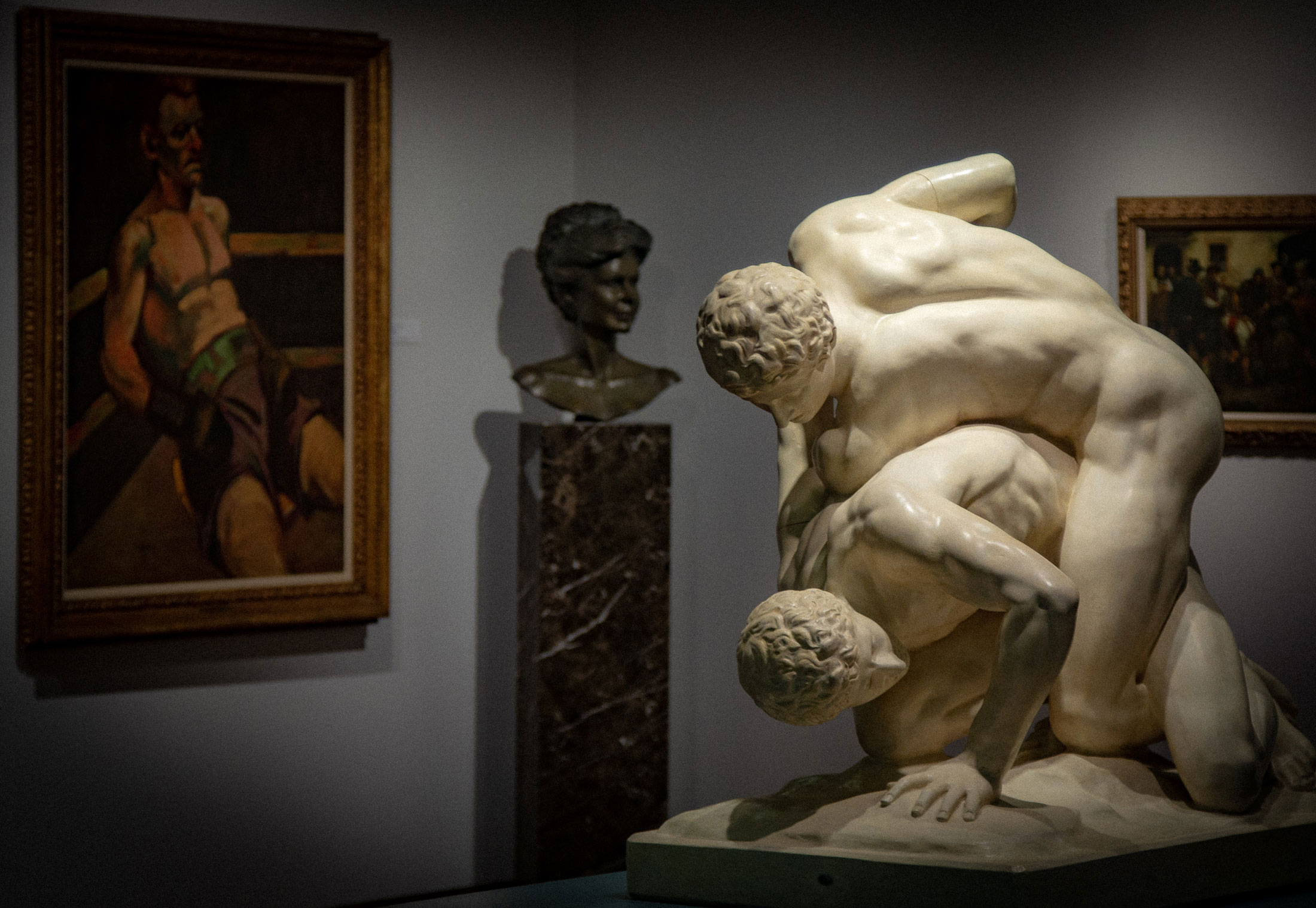Front view of The Battle Cast the Wrestlers statue, on loan from the Blanton Museum of Art, located in the Teresa Lozano Long Art Gallery; a bust of Betty Weider, from the Weider Art Collection, is in the background.