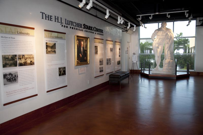 The statue of the Farnese Hercules in the main lobby; six panels telling the story of H.J. Lutcher Stark and a painting of H.J. Lutcher Stark are visible on the left.