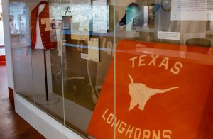 A display case, in the main lobby, including the varsity letter jacket worn by H.J. Lutcher Stark, football cleats; and, from the Clyde Rabb Littlefield Collection, one of the Texas Longhorns blankets used by the undefeated 1914 University of Texas football team, the first time the term Longhorns was used, in the 1914: A Perfect Season Gallery.
