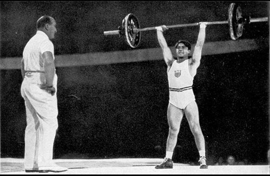 A United States weightlifter jerking a barbell overhead, while a coach looks on, at the 1936 Summer Olympics.