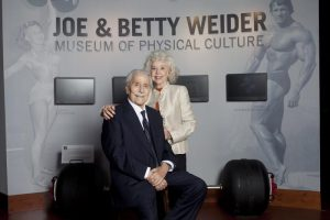 Joe and Betty Weider in front of the sign for the Joe and Betty Weider Museum of Physical Culture, featuring bodybuilders Pudgy Stockton and Arnold Schwarzenegger, in the main lobby.
