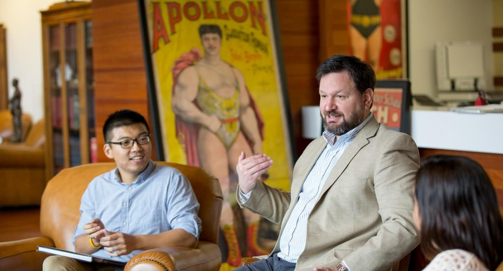 Graduate student Andrew Hao, University of Texas professor Thomas M. Hunt and another graduate student in the Reading Room; a poster featuring strongman Apollon (Louis Uni), from the Todd Poster Collection, is in the background.