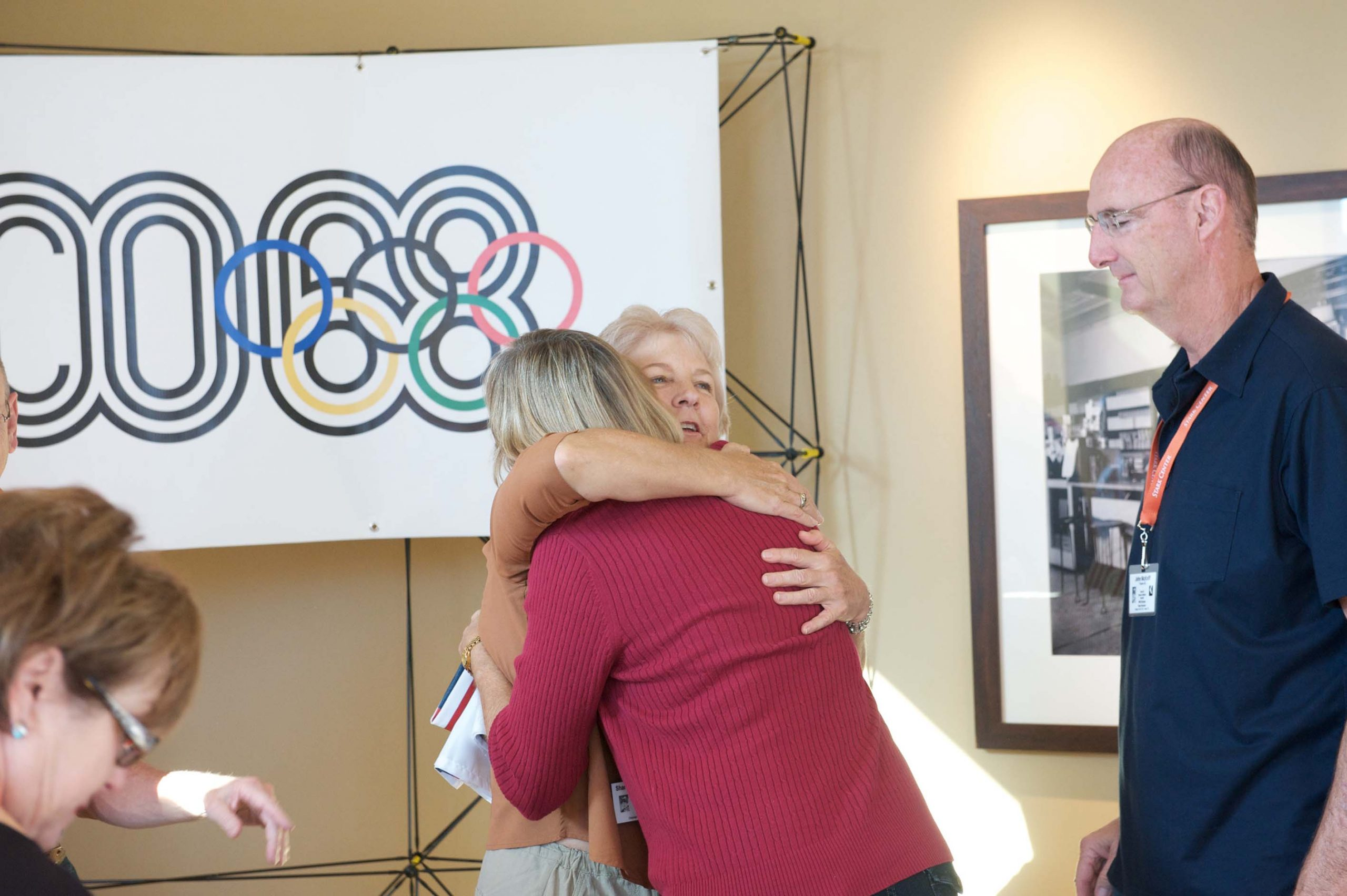 Five people, including two hugging, at the 1968 U.S. Olympic Team 2012 Reunion.