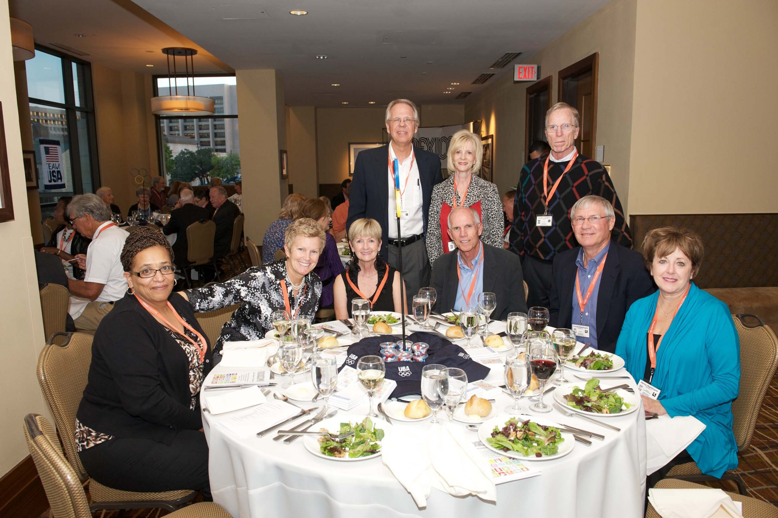 Sixteen people at two tables at the 1968 U.S. Olympic Team 2012 Reunion.