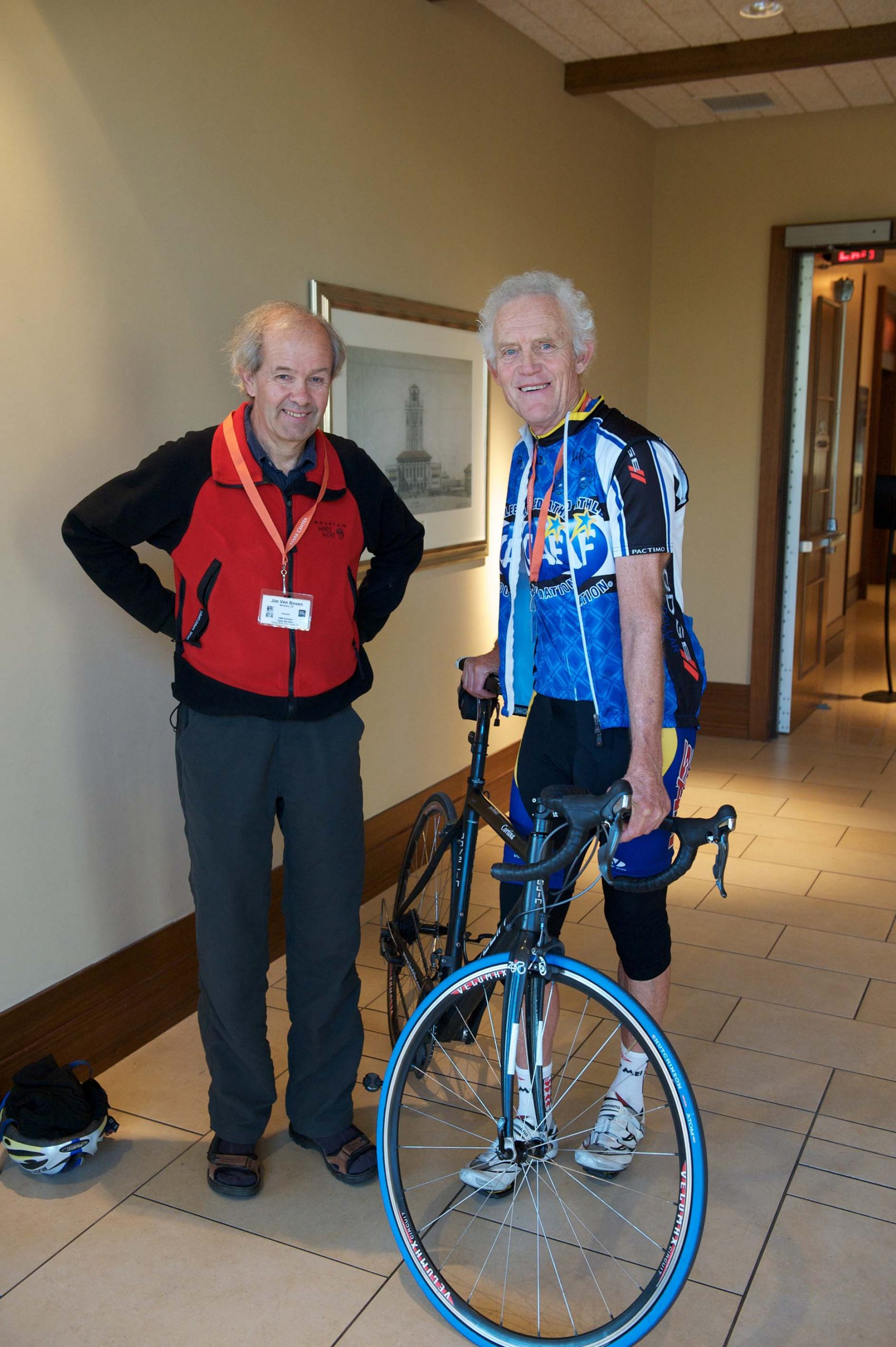 Photograph of two people, including one on a bike, at the 1968 U.S. Olympic Team 2012 Reunion.