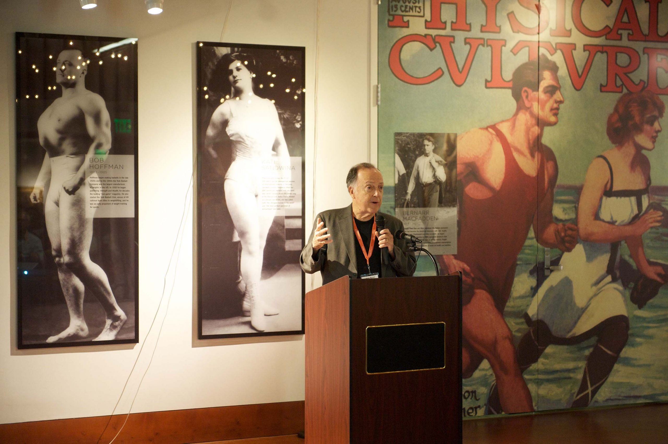A man speaking in front of the Wall of Icons, in the man lobby, at the 1968 U.S. Olympic Team 2012 Reunion.