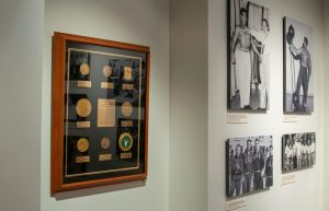 Medals won by weightlifter Tommy Kono and four photographs of Kono and others, in the Strength and Friendship: Remembering Tommy Kono Gallery.
