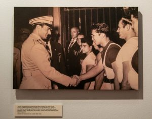 Weightlifter Tommy Kono shaking hands with a soldier, in the Strength and Friendship: Remembering Tommy Kono Gallery.