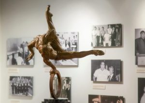 A scuplture of a gymnast in the Strength and Friendship: Remembering Tommy Kono Gallery, nine photographs illustrating different facets of weightlifter Tommy Kono's life are in the background.