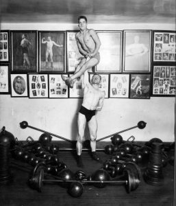 Strongman Ottley Coulter (the understander) and handbalancer Charles Shaffer (on top on Coulter's right hand) handbalancing in a gym, from the Ottley Coulter Collection.
