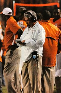Former University of Texas football coach Mack Brown taking notes on the sideline, from the Mack Brown Collection.