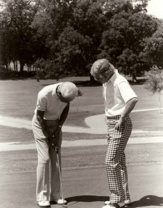 Former University of Texas golf coach Harvey Penick, and former University of Texas golfer Tom Kite, on the putting green, from the Harvey Penick and Tinsley Penick Golf Collection.