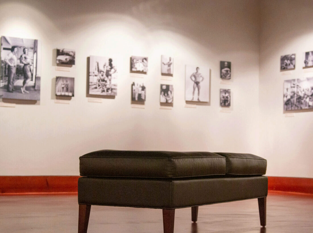 A leather bench in the Joe and Betty Weider Museum of Physical Culture, fourteen photographs, including one of publisher Joe Weider and bodybuilder Arnold Schwarzenegger, are in the background.