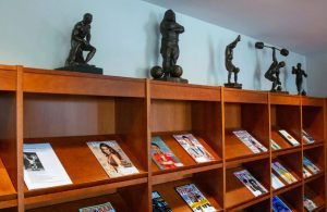 Five statues, including one of strongman Louis Cyr, and magazines on the open shelves of the library, in the Reading Room.