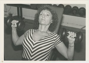 Bodybuilder Doris Barrilleaux about to press two dumbbells, on an inclined bench, from the Doris Barrilleaux Collection.