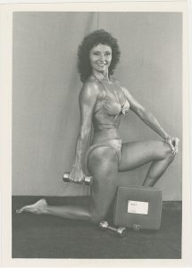 Bodybuilder Doris Barrilleaux posing, in a bikini, while holding a dumbbell, from the Doris Barrilleaux Collection.
