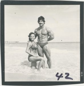 Bodybuilder Doris Barrilleaux, in a bikini, at the beach with a male bodybuilder, in a swimsuit, from the Doris Barrilleaux Collection.