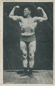 Wrestler and strongman George Hackenschmidt, in a front double biceps pose, from the George Hackenschmidt Collection.