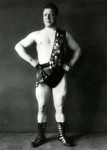 Wrestler and strongman George F. Jowett, wearing a sash covered by championship medals, from the scrapbooks from the George F. Jowett Collection.
