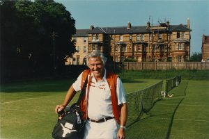 Former University of Texas tennis coach Dave Snyder, standing with a bag of tennis rackets on a tennis court, from the Wilmer Allison and Dave Snyder Tennis Collection.