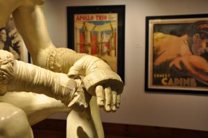 Battle Cast sculpture of the Boxer, on loan from The Blanton Museum of Art, in the Teresa Lozana Long Art Gallery; posters for strongmen the Apollo Trio and strongman Ernest Cadine, from the Todd Poster Collection, are in the background.