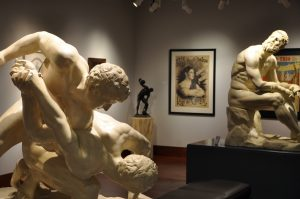 Battle Cast sculptures of the Wrestlers and the Boxer, on loan from The Blanton Museum of Art, in the Teresa Lozano Long Art Gallery; posters for strongman Ruy da Cunha and strongmen the Apollo Trio, from the Todd Poster Collection, are in the background.