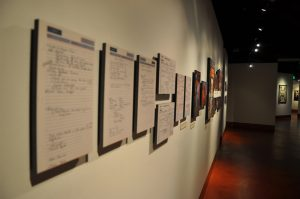 Seven panels of coaching memos and eight photographs of various University of Texas coaches, in the Coaching Greatness Gallery.