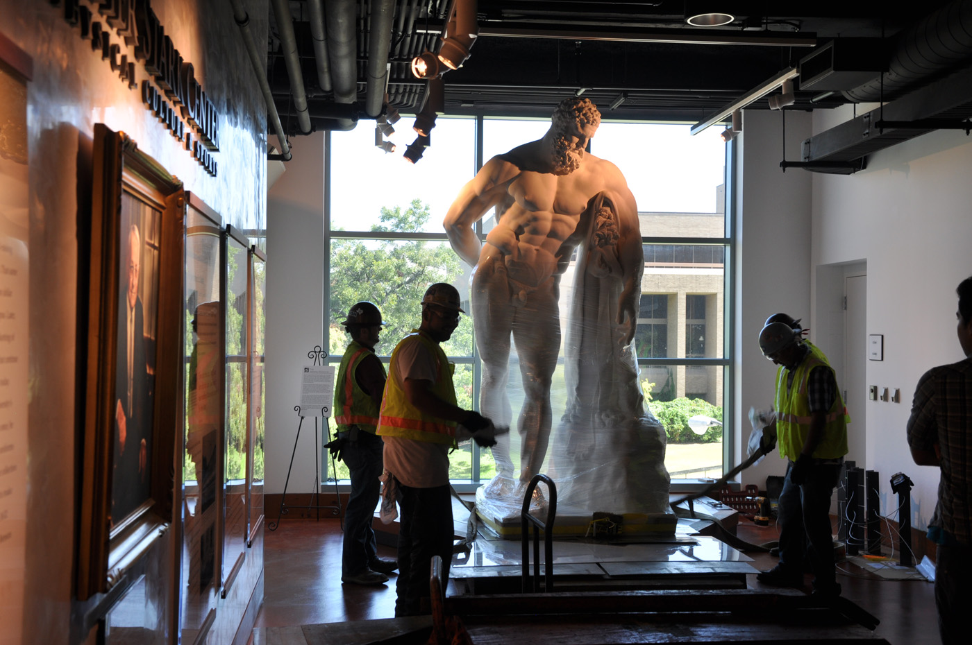 Front view of the statue of the Farnese Hercules wrapped and being moved, while four men work on it, in the main lobby.