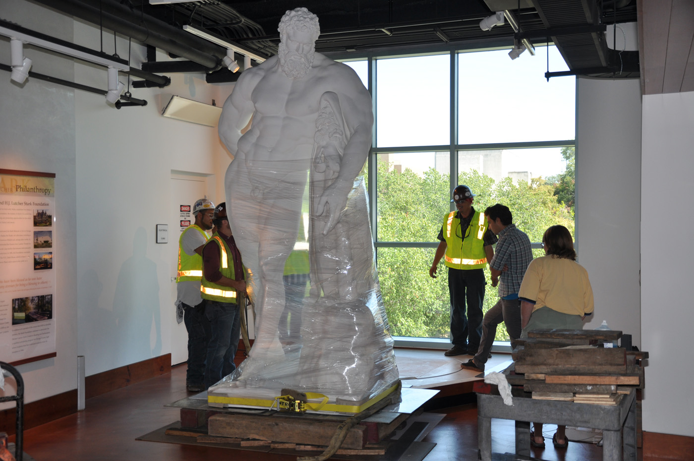 Front view of the statue of the Farnese Hercules wrapped and being moved, while three men, Kyle Martin, and Kim Beckwith all work on it, in the main lobby.