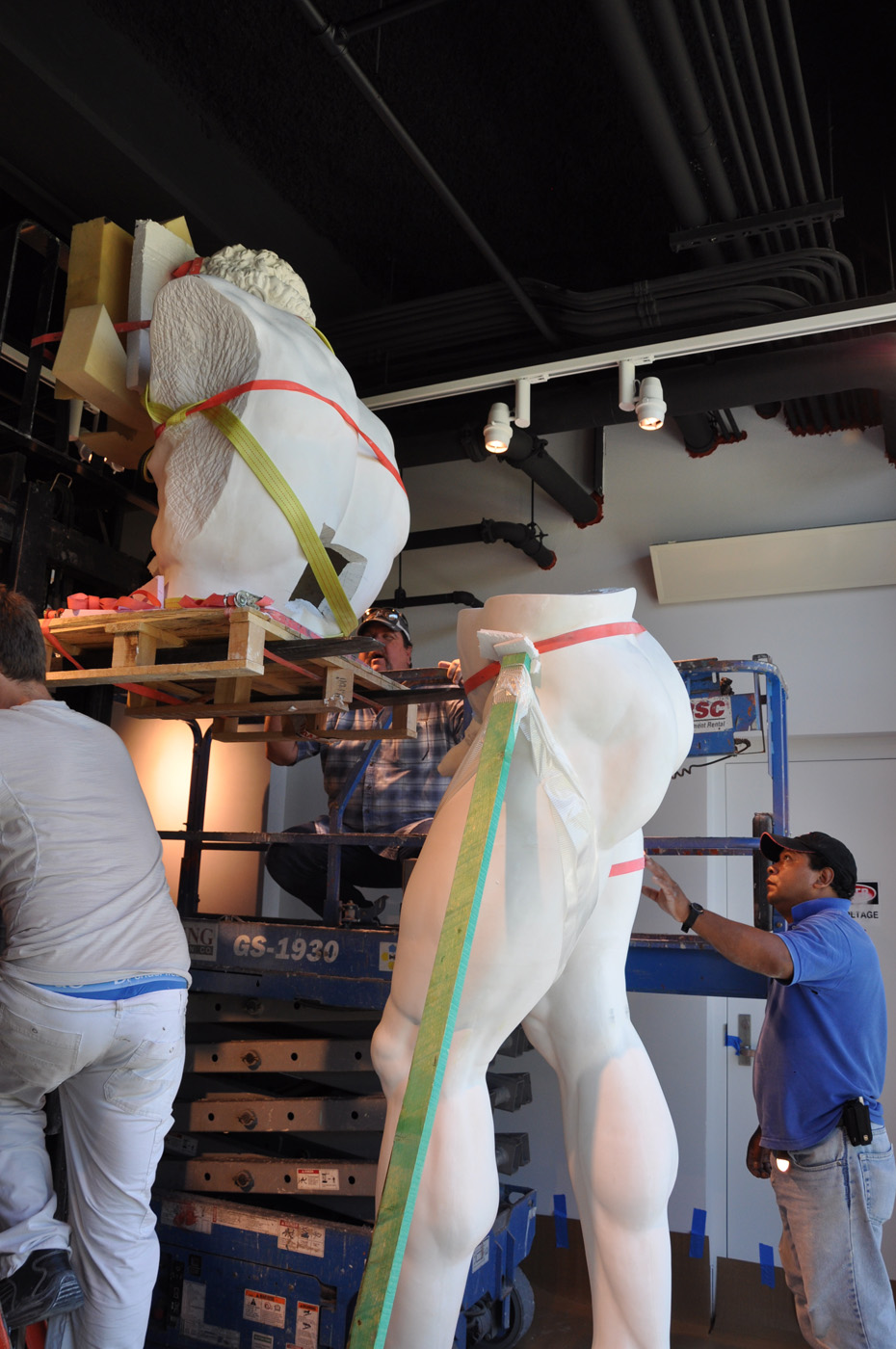 Side view of the bottom half of the statue of the Farnese Hercules, waiting for the top half to be installed, while three me work on it, in the main lobby, in 2009.