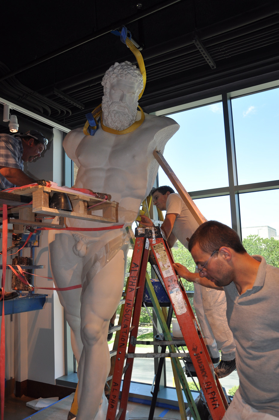 The statue of the Farnese Hercules strapped and being installed, while three men work on it, in the main lobby, in 2009.