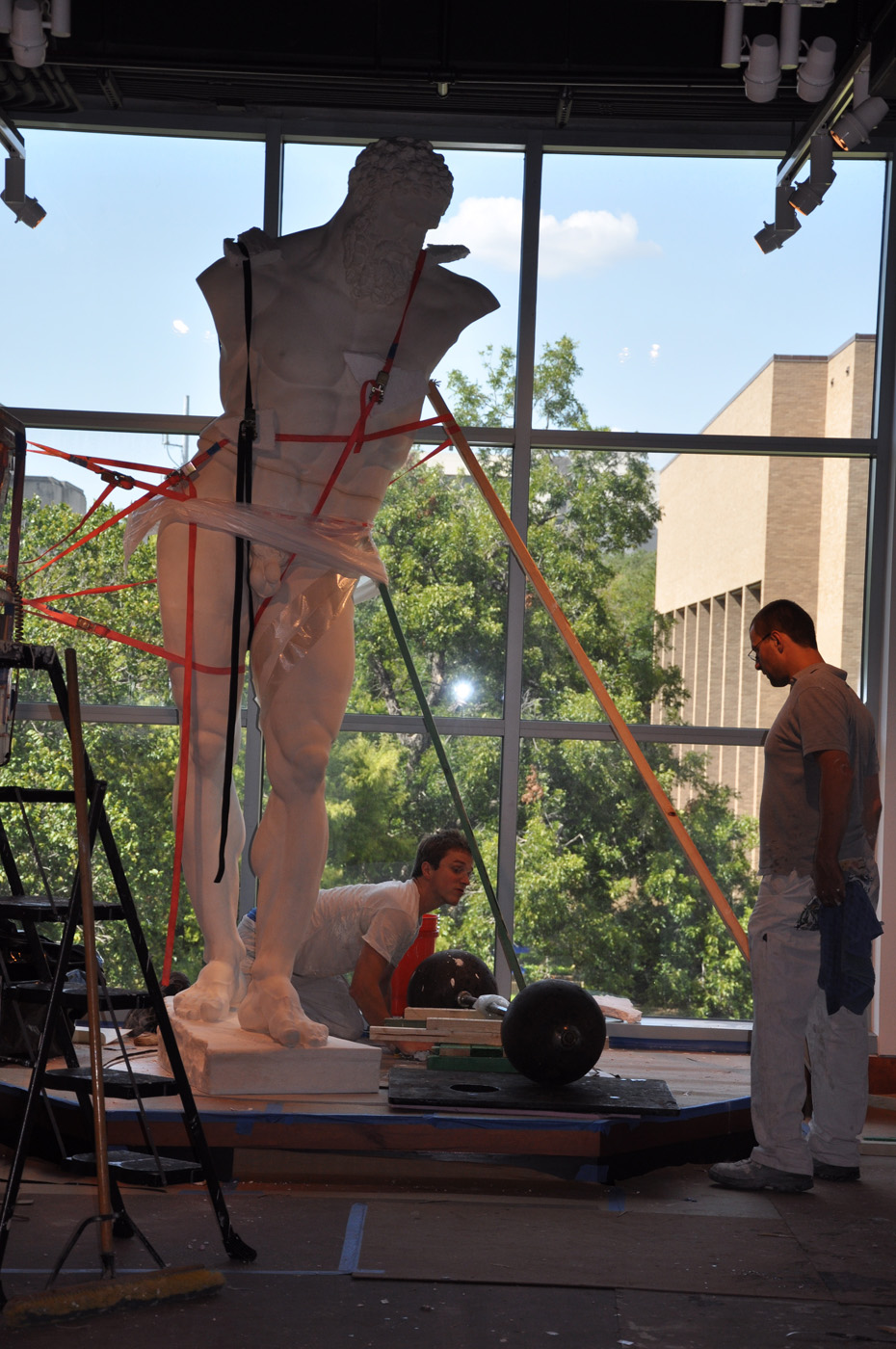 Front view of the statue of the Farnese Hercules strapped and being installed, while two men work on it, in the main lobby, in 2009.
