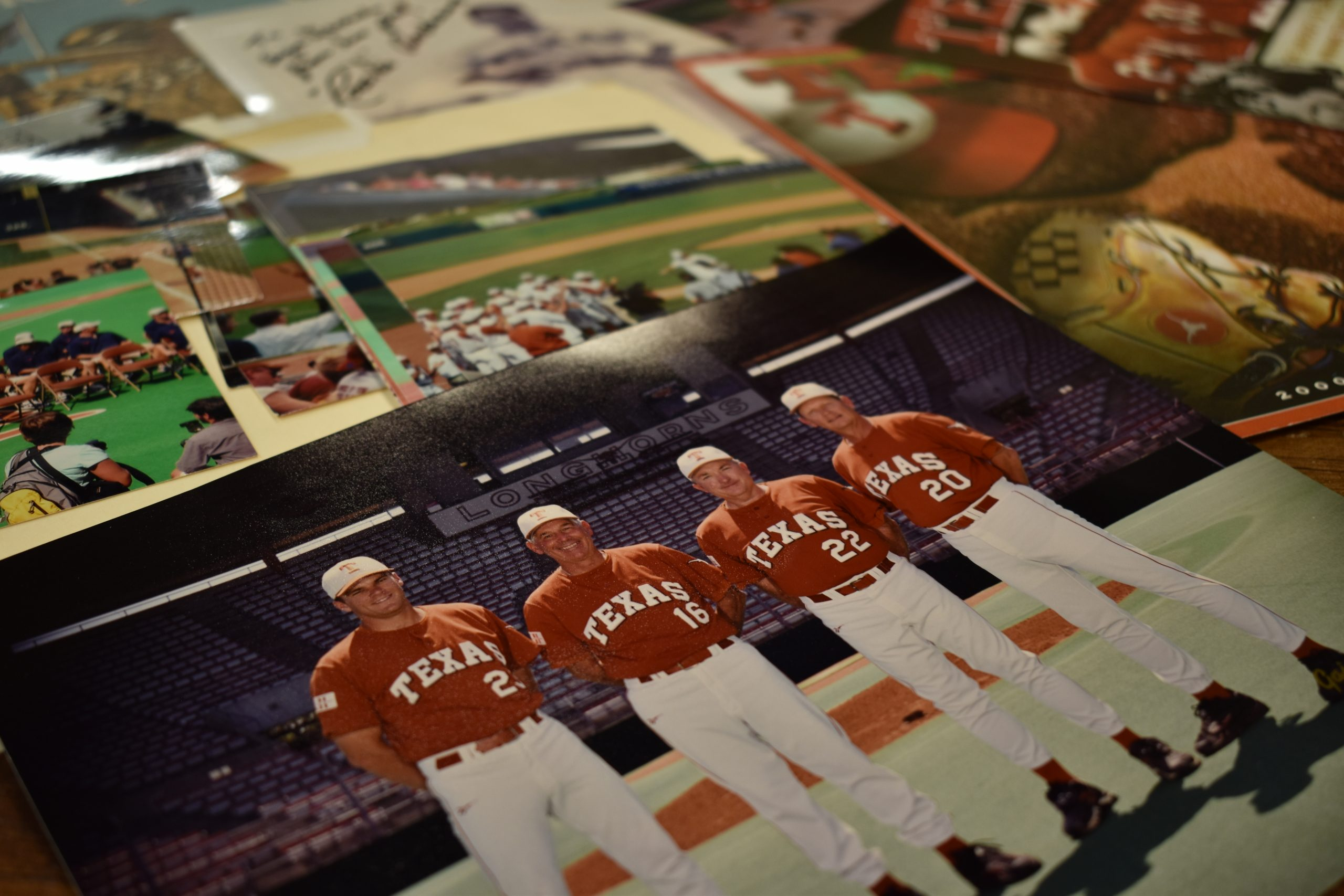 Two baseball media guides, a newspaper article and six photographs, relating to former University of Texas baseball coach Augie Garrido, from the Coach Augie Garrido Baseball Collection.