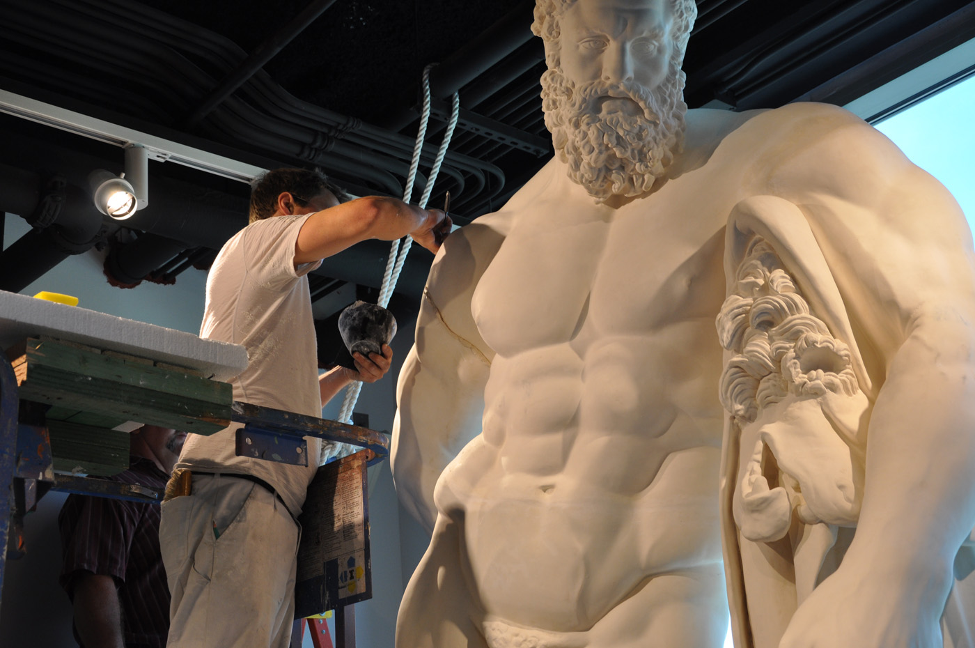 Front view of the top half of the statue of the Farnese Hercules being installed, while two men work on it, in the main lobby, in 2009.