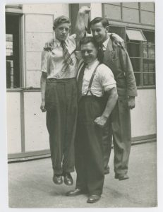 Bodybuilder Stanley Rothwell, lifting two other men up with his right arm, from the Stanley Rothwell Collection.