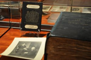 Likely strongman and wrestler George Hackenschmidt's British passport, a photograph of Hackenschmidt and his wife Rachel, and the George Hackenschmidt Scrapbook, all from the George Hackenschmidt Collection, in a display case, in the Strong Men, Strong Women Gallery.