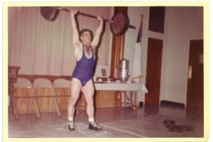 Weightlifter Bob Samuels pressing a barbell overhead with two hands, from the Bob Samuels Collection.