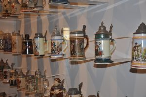 Twenty-eight physical culture themed steins of various sizes, from the Todd Art Collection, in a display case, in the main lobby.