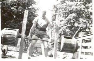 Weightlifter Bob Peoples, using his wooden barbell, with a wooden power rack that Peoples invented.