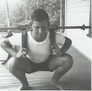 Likely a young Bob Peoples, using the shoulder rack arrangement to hold a barbell for heavy squats, invented by weightlifter Peoples, from the Peary and Mabel Rader Collection.