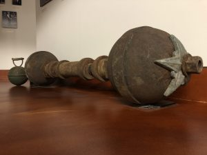 Warren Lincoln Travis' show barbell viewed at an angle to show full length but also the start detailing on the end of the globe closest to the camera