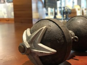Warren Lincoln Travis' show dumbell that he lifted using a harness viewed at an angle to show most of the dumbell and also the star detailing on the globe closest to the camera