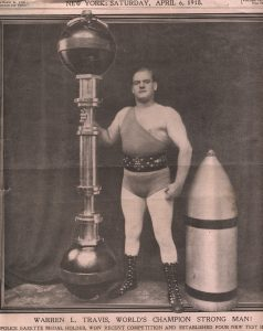 Clipping of Warren Lincoln Travis from the Police Gazette, Saturday, April 6th, 1918, standing and holding a barbell up vertically