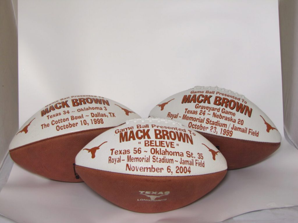 "Three commemorative ""Game Ball"" footballs given to Mack Brown for the 1998 Red River Showdown at The Cotton Bowl   - Dallas (Texas vs Oklahoma),  the 1999 Graveyard Game (Texas vs Nebraska), and the 2004 Believe Game (Texas vs Oklahoma) game"