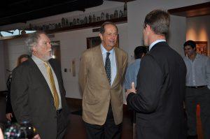 Senator Bradley and Terry Todd listen to Ross Ohlendorf in the Stark Center lobby.