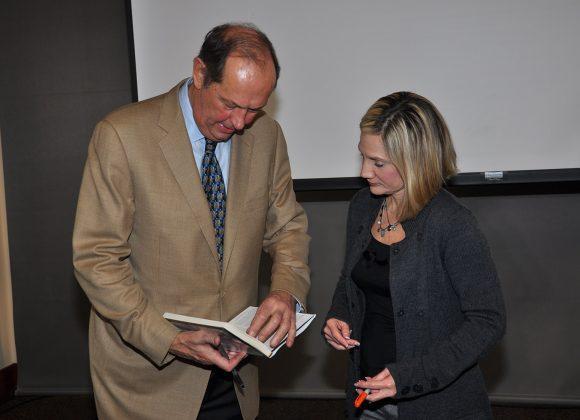 Bill Bradley with Karen Aston looking through a book